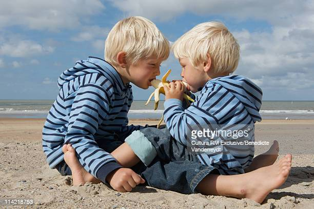 Two little brothers sharing a banana