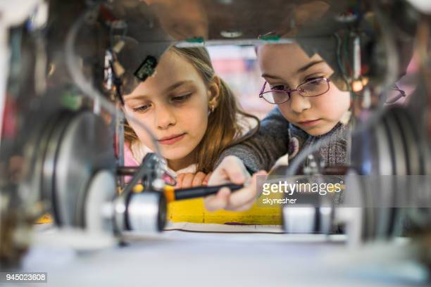 two little engineers working in team while repairing a robot. - stem stock photos and pictures