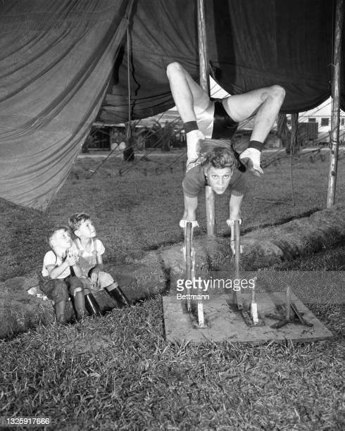 Two little gate crashers get a peep behind the scenes during a rehearsal by Elsie Alzana, one of a family of high wire performers. She is working out...