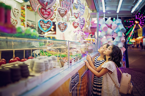 Two little girls are looking sweets in the candy wagon at the fun fair - gettyimageskorea