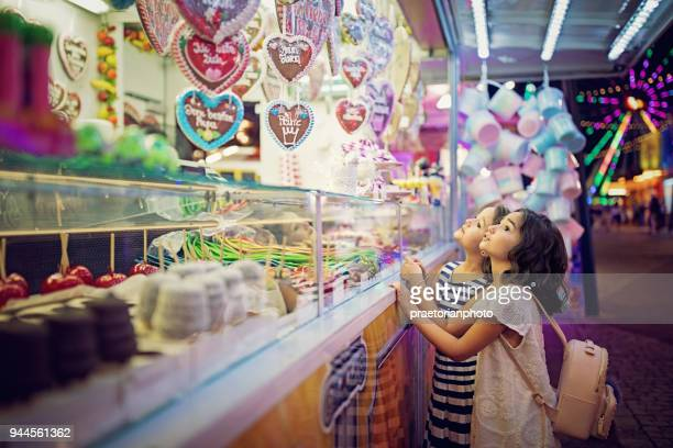 two little girls are looking sweets in the candy wagon at the fun fair - traveling carnival stock pictures, royalty-free photos & images