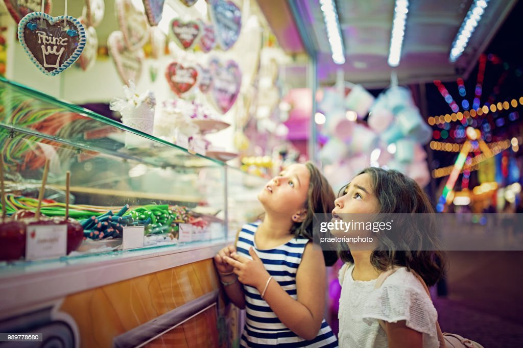 Two little girls are looking sweets in the candy wagon at the fun fair : Stock Photo