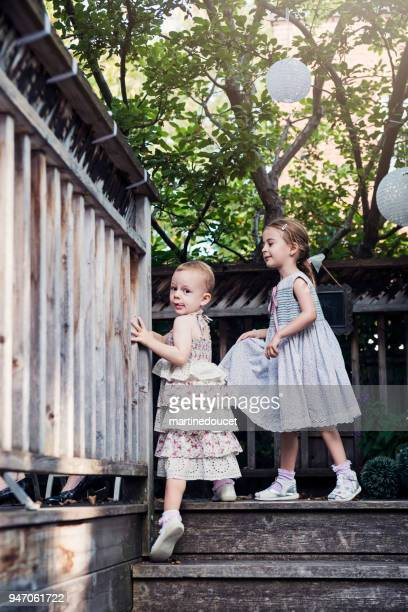 Two little girls climbing up stairs outdoors.