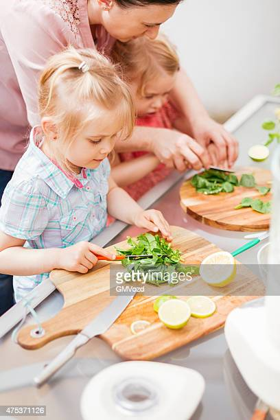 Two Little Girls Cutting Fruits and Vegetables for Preparing Smoothies