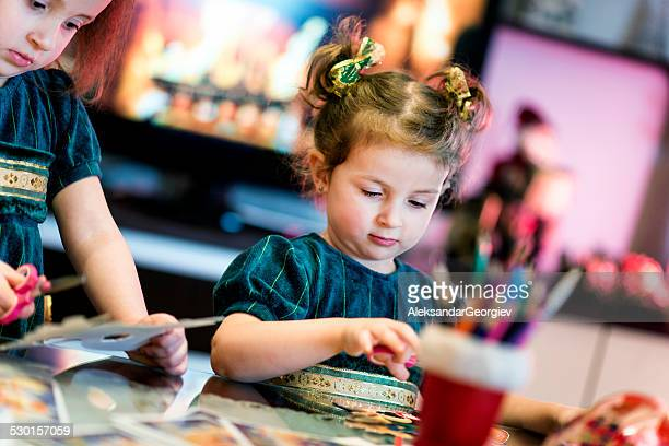 Two Little Girls Cutting Paper Snowflakes and Making Christmas Gifts