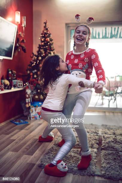 two little girls dancing by christmas tree on new year morning - budding tween stock photos and pictures