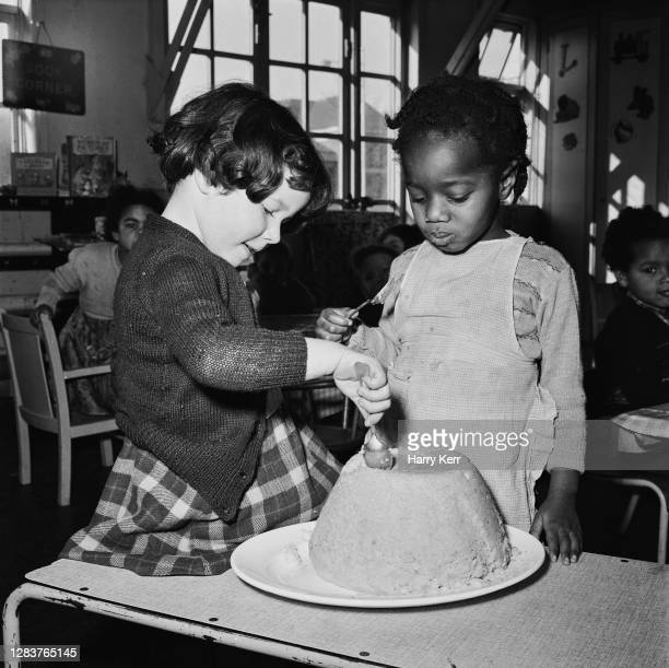 Two little girls dig into a cake at the Brixton Day Nursery on Coldharbour Lane in Brixton, south London, 1955. Four years earlier there were no...