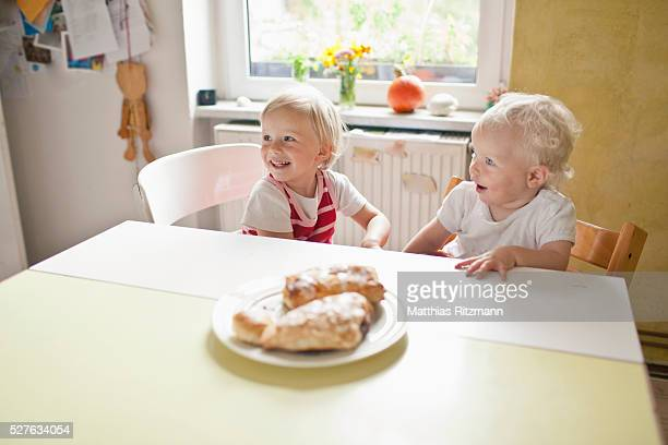 Two little girls (6-12 months, 1-2) eating breakfast