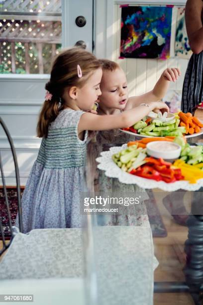 Two little girls eating raw vegetables at a buffet.