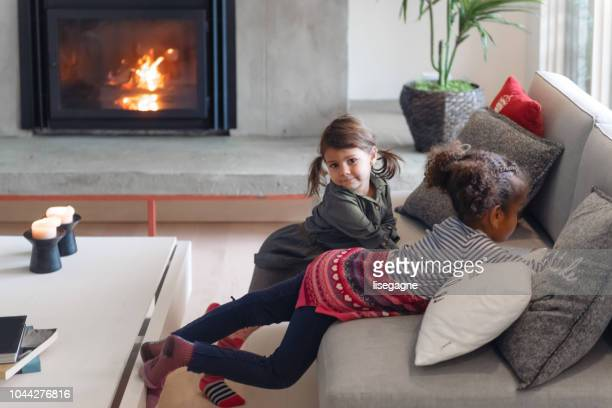 two little girls hanging out during thanksgiving preparation - fireplace stock pictures, royalty-free photos & images