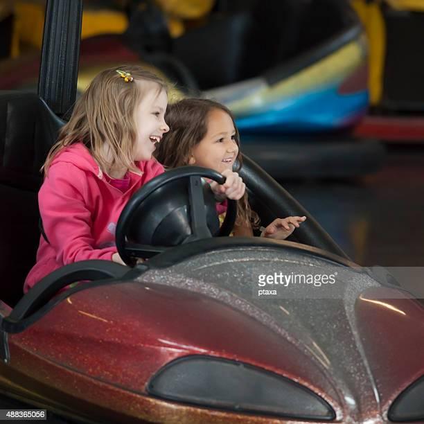 Two little girls having fun riding bumper cars