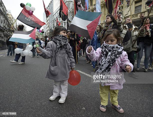 Two little girls hold Palestinian flags during a protest demanding to Israel to stop the 'genocide' in the Gaza strip outside the Israeli embassy in...