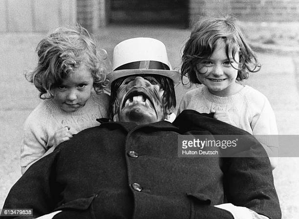 Two little girls hold up their Guy which was made to celebrate Guy Fawkes Day