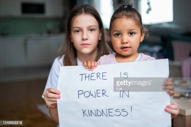 two little girls holding a poster with handwritten message:there is power in kindness! - anti racism stock pictures, royalty-free photos & images