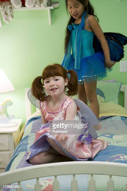 two little girls in costumes on bed - hairy little girls stock photos and pictures