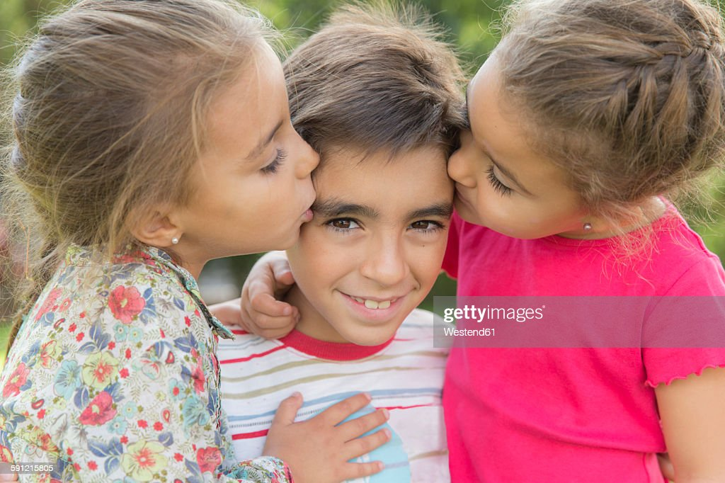 Two Little Girls Kissing A Boy High-Res Stock Photo -8078