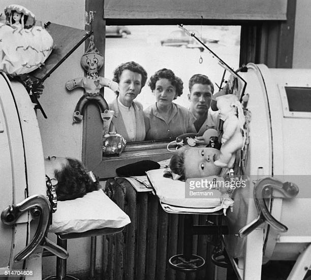 Two little girls lay in Iron Lung Machines while being treated for Polio. Their family looks in from the window outside.