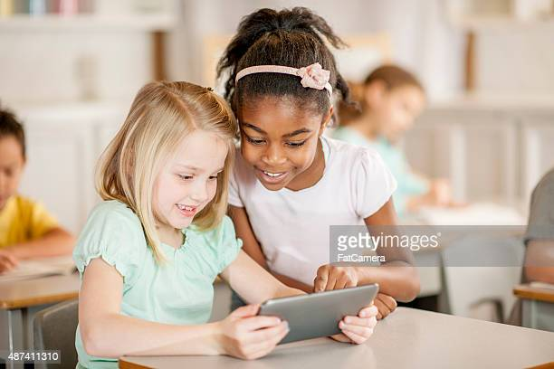 Two Little Girls Looking at a Tablet in Class