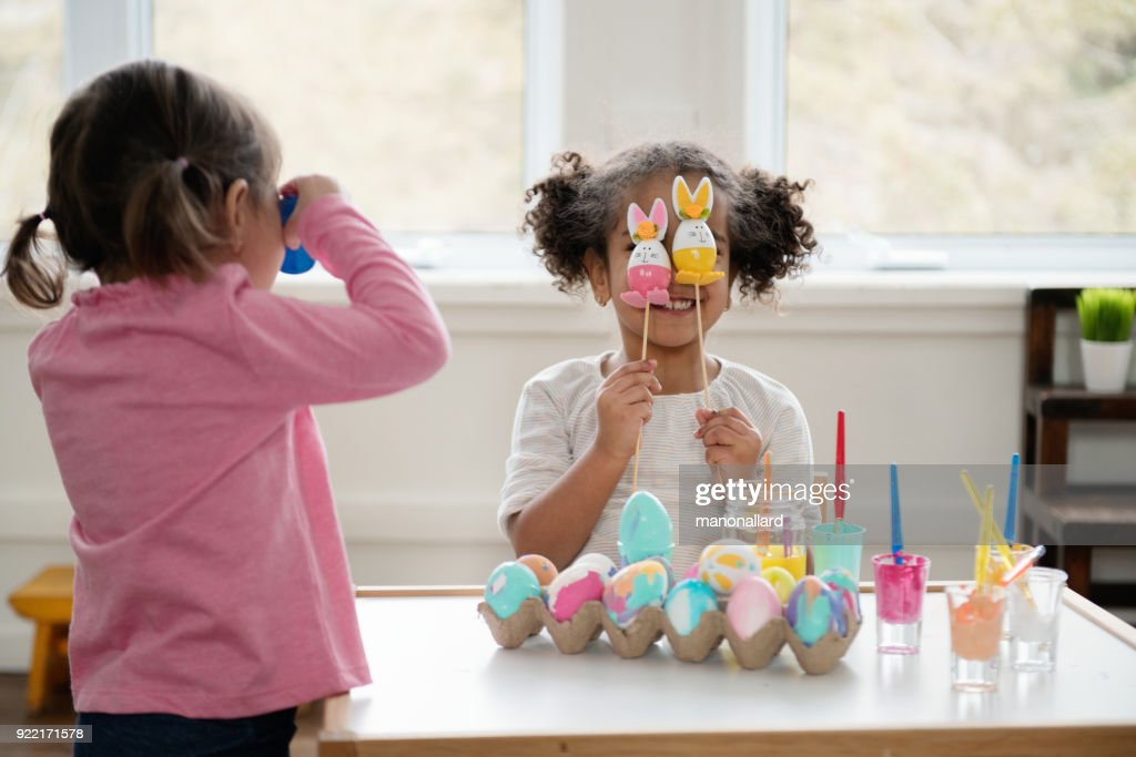 Two Little girls looking through Easter eggs. : Stock Photo