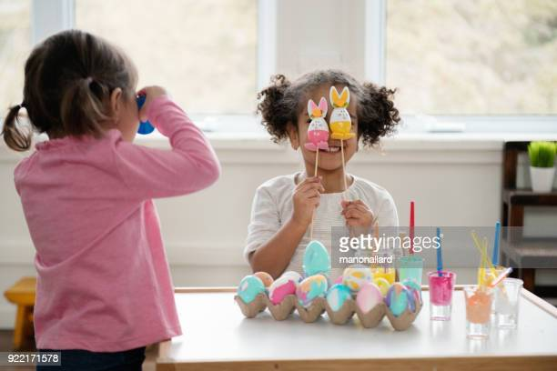 Two Little girls looking through Easter eggs.