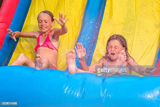 Two little girls on an inflatable slide