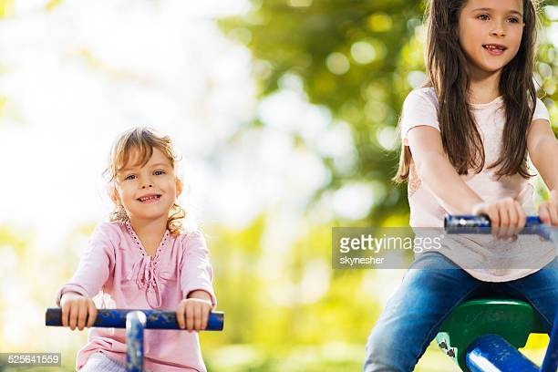 Two little girls on seesaw.