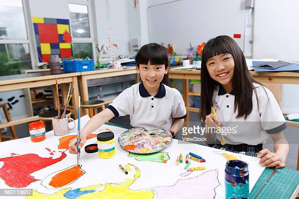 Two little girls painting in the classroom