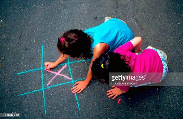 Two Little Girls Play TicTacToe With Colored Chalk