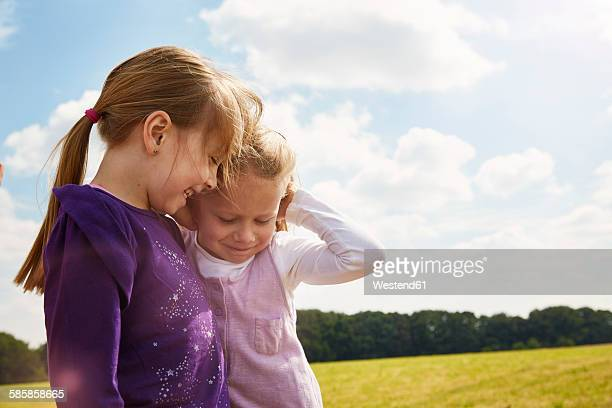 Two little girls playing on a meadow
