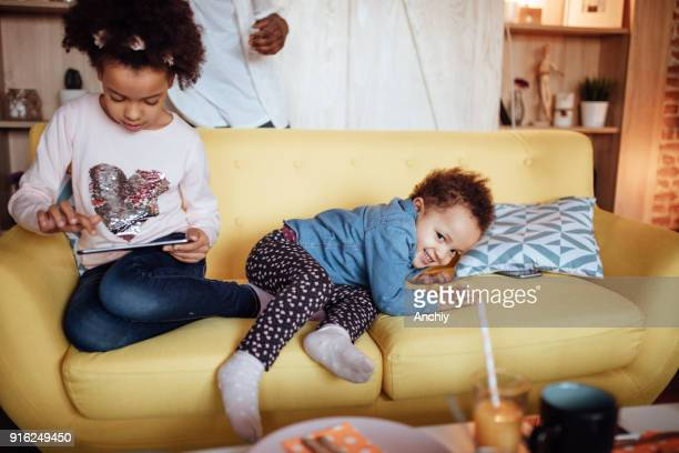 Two little girls playing on the sofa