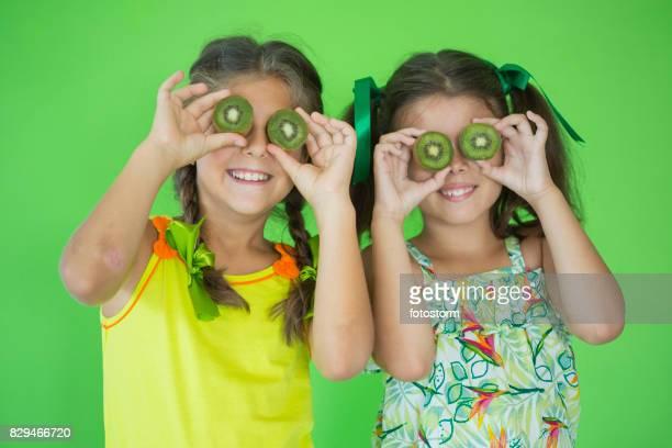 Deux petites filles jouant avec kiwi