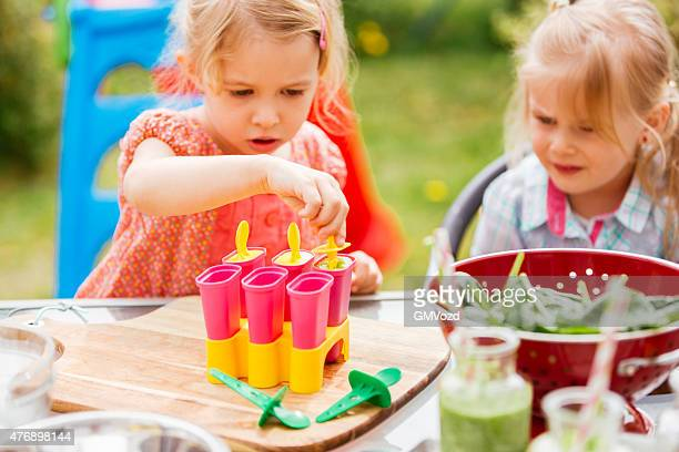 two little girls preparing popsicles outside - ice cube family stock pictures, royalty-free photos & images