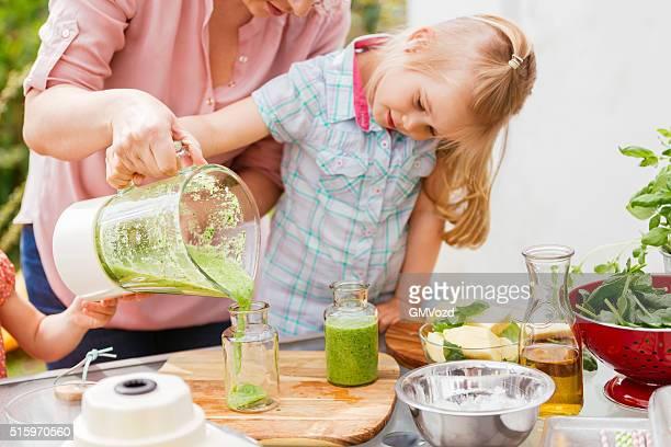Zwei kleine Mädchen mit ihrer Mutter vorbereiten Smoothies