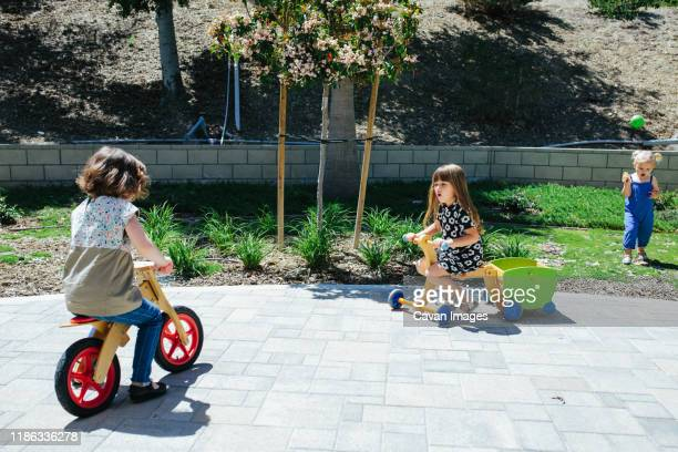 two little girls ride wooden push bikes outside - calabasas stock pictures, royalty-free photos & images