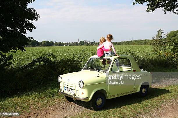 Two little girls sit on the open deck of a Vespa 400 and look at the sunny landscape The twin sisters hug The subcompact 'VESPA 400' was built in the...