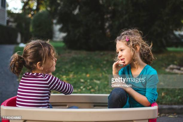 two little girls sit together having a conversation inside a wagon - family with two children stock pictures, royalty-free photos & images