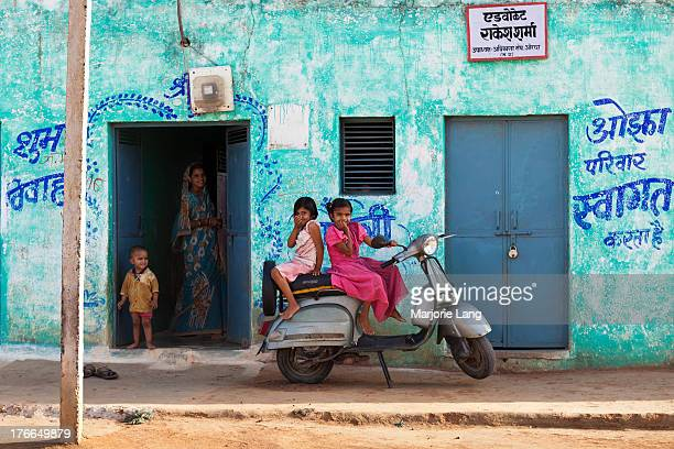 CONTENT] Two little girls sitting and smiling on an old scooter and their mother at the doorstep in front of their colorful blue house in Orchha...