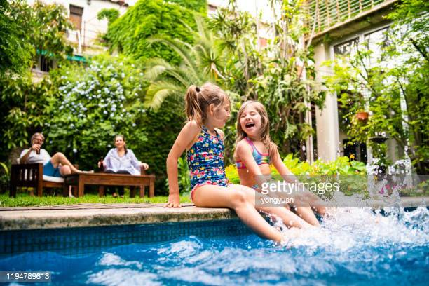 two little girls sitting at poolside and splashing water with legs - front or back yard stock pictures, royalty-free photos & images