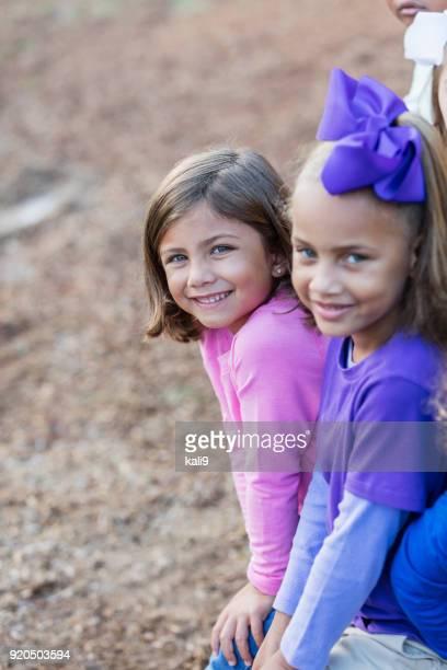 zwei kleine mädchen in die kamera lächeln - schulkind nur mädchen stock-fotos und bilder
