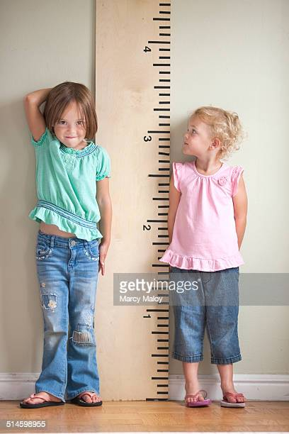 Two little girls standing next to a big ruler.