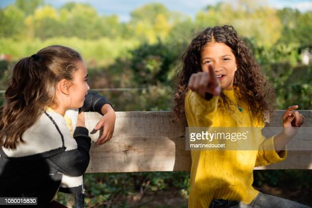 """two little girls strolling in old trailer in field. - """"martine doucet"""" or martinedoucet stock pictures, royalty-free photos & images"""