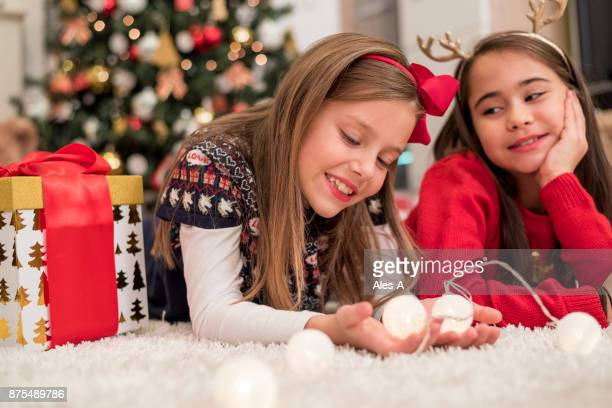 Two little girls under the Christmas tree
