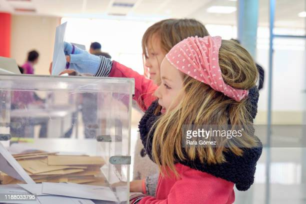 two little girls voting in the electoral college - demokratie stock-fotos und bilder