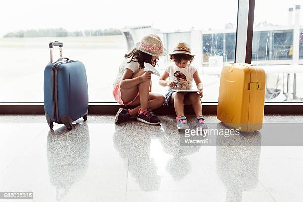two little girls waiting at airport, playing with digital tablet - toddler at airport stock pictures, royalty-free photos & images