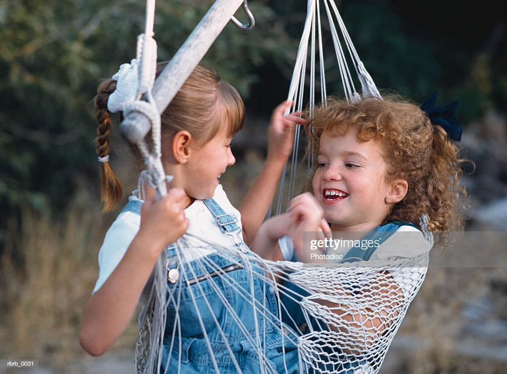 two little girls wearing denim overalls and white shirts are playing in a hammock while laughing and smiling at each other : Stockfoto