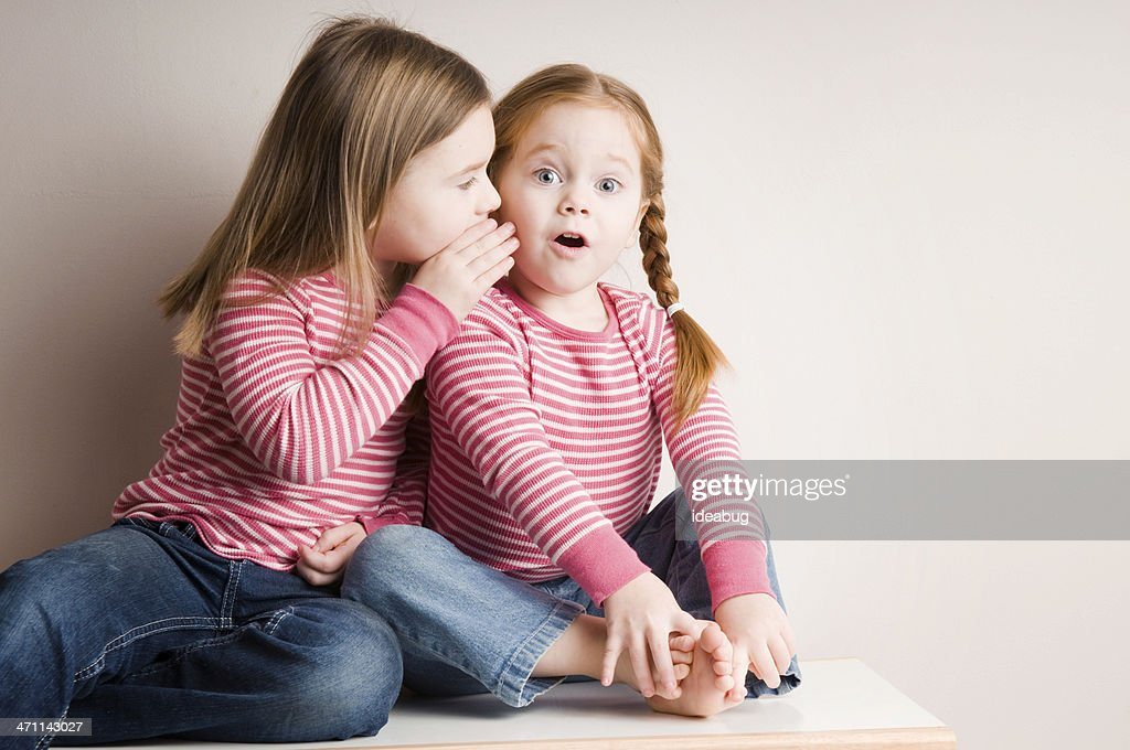 Two Little Girls Whispering Surprising Secrets : Stock Photo