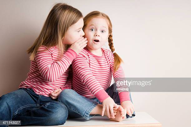 Two Little Girls Whispering Surprising Secrets
