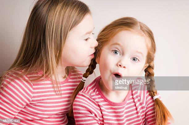 two little girls whispering surprising secrets - girl strips stock pictures, royalty-free photos & images