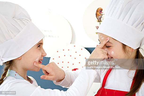 Two little girls with chef's hat kidding around, Munich, Bavaria, Germany