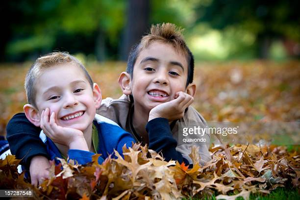Hispanic Brothers Hugging in Pile of Fall Leaves, Copy Space